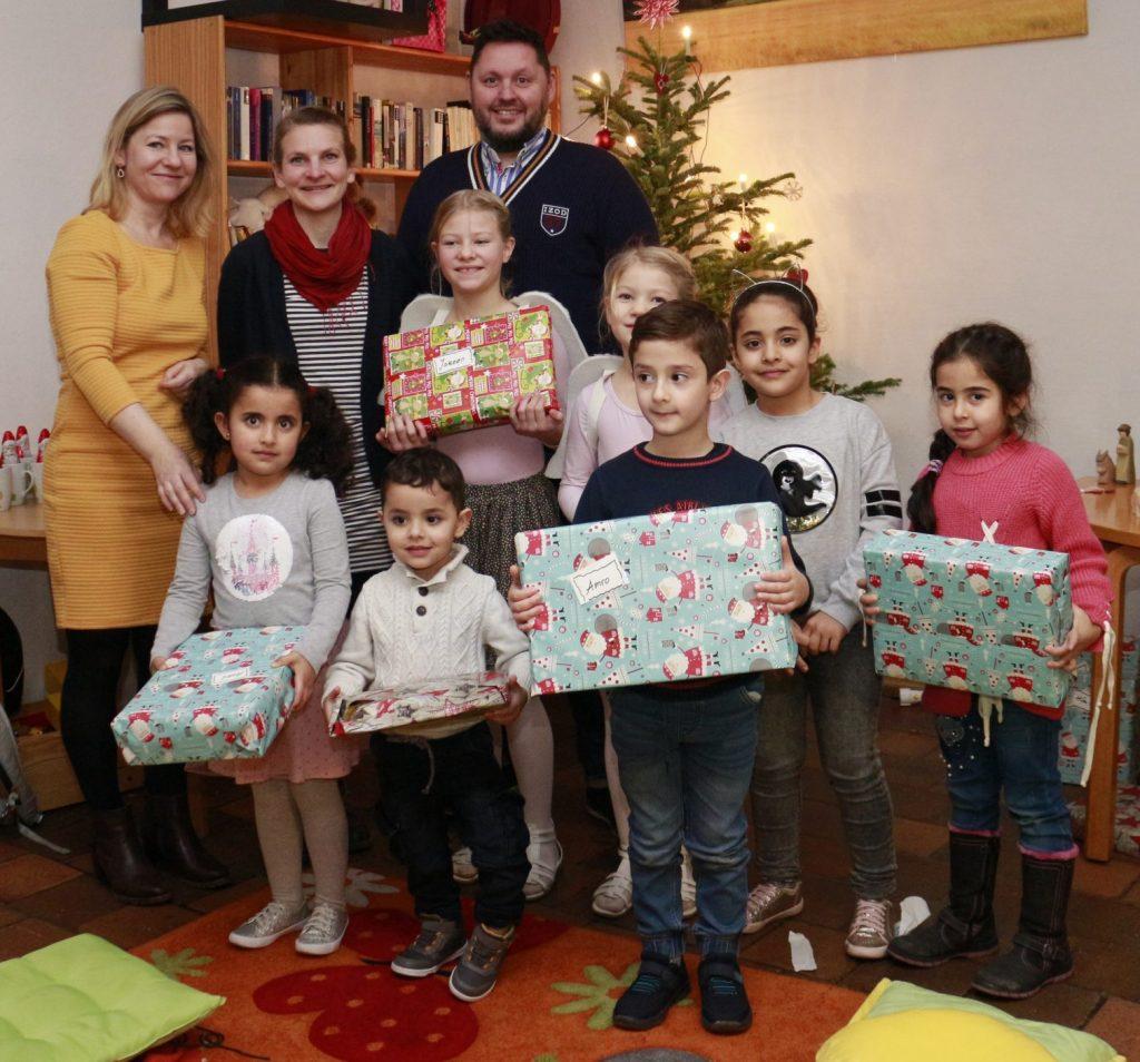 Organisatoren und beschenkte Kinder bei der Weihnachtsfeier